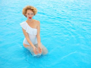 beautiful smiling redhead (ginger) woman portrait enjoying life in the swimming pool in the summer day. Summer, relax, wellness, travel, recreation concept